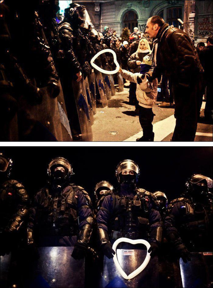 a-romanian-child-hands-a-heart-shaped-balloon-to-riot-police-during-protests-against-austerity-measures-in-bucharest